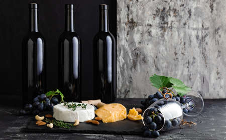Wine bottles cheese nuts and grapes on slate board. Wine bar snacks. Wine composition on dark rustic concrete background with copy space