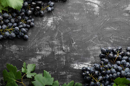 Black juicy grapes on vintage dark concrete background. Frame made of grapes. Copy space for text or menu on black scuffed background. Banco de Imagens - 161030123