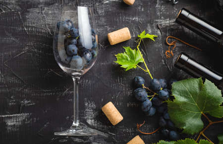 Wine glass full of grapes inside. Wine bottles, grape bunches with leaves and vines wine corks on dark rustic concrete background. Flat lay wine composition on black stone table. Long web banner.