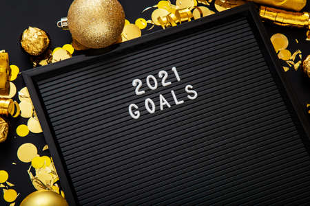 2021 Goals text on black Letter Board in Christmas festive decor, confetti ball. New year 2021 goals Banco de Imagens