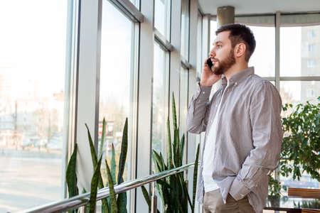 Smart beard Caucasian man is talking by smartphone. Businessman freelancer have Phone conversation in urban modern office in meeting room near window.