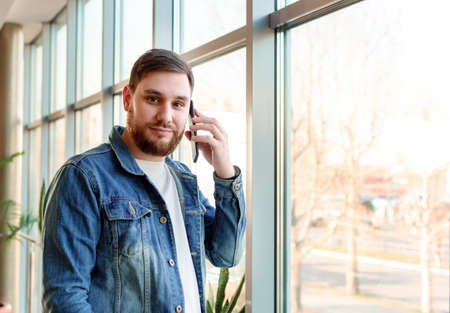Young man making call, talking by phone indoors near window wall in casual jean jacket. Caucasian bearded business man in modern city office have mobile conversation. Banco de Imagens