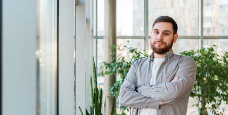 Caucasian man standing near full length window in modern office with plants. Successful bearded young man crossed arms. Handsome businessman smart man in casual shirt. Long web banner with copy space Banco de Imagens