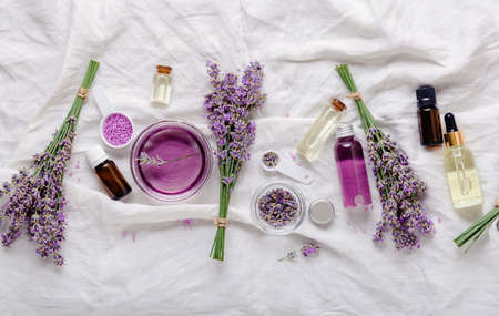 Lavender skincare cosmetics productsoils serum and lavender flowers on white fabric. Set natural spa beauty products. Lavender essential oil, serum, body butter, massage oil, liquid. Flat lay Banco de Imagens
