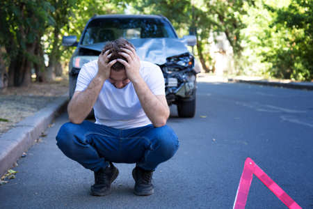 Driver man in front of wrecked car in car accident. Scared man holding his head after auto crash. Tragedy car collision. Dangerous road traffic situation.