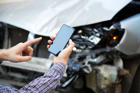 Man holds mockup mobile phone screen in hands after car accident. Calling insurance service in web app to place of car accident. Smartphone in front of wrecked car Banco de Imagens