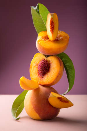 Flying fresh ripe peach in slices and whole fruits with green leaves. Peach fruit levitation on pink color background. Minimalistic composition with tropical peach fruits.