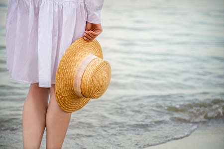 Straw hat in female hand on seashore at sunset. Unrecognizable Woman in white beach dress having rest at sunset on sea beach. Woman enjoys vacation and freedom on sunset sea beach. Copy space