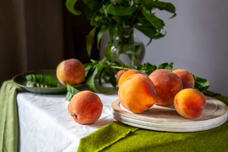 Peaches on table in kitchen near window. Rustic minimalism food peach fruits with leaves on wooden board on tablecloth. Harvest of Ripe juicy peaches. Still life Peaches fruit Banco de Imagens