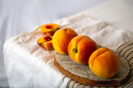 Peaches on table in kitchen near window. Rustic minimalism food peach fruits with leaves on wooden board on tablecloth. Harvest of Ripe juicy peaches. Long web banner Banco de Imagens