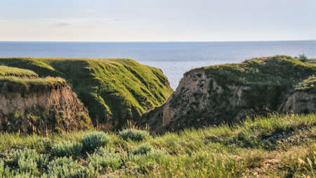 Landscape view of cape from clay mountains and cliffs on sea. Seascape of coast from green meadows. Clay rock in front of sea. Sea view horizon. Secluded nature tourism. Long web banner Banco de Imagens