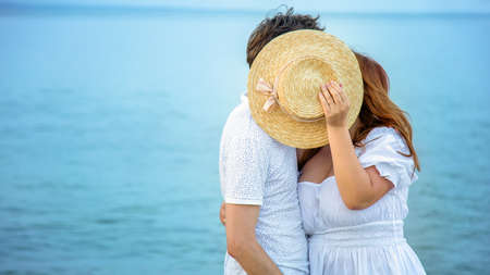 Loving couple have kiss hiding behind yellow straw hat on sea background. Unrecognizable Woman and Man Love, valentines day romantic relationship in honeymoon.