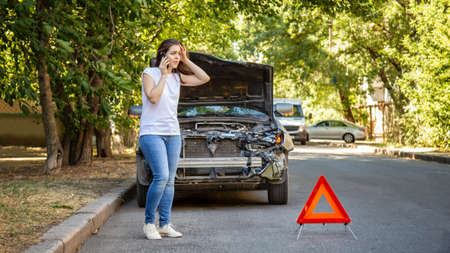 Driver woman in front of wrecked car in car accident. Scared woman in stress holding her head after auto crash calling to auto insurance for help. Dangerous road traffic situation. Long web banner