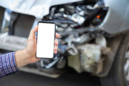 White mockup screen mobile phone in male hands after car accident. Mock up for Insurance service, driving school, tow truck call or web app above car accident. Smartphone in front of wrecked car