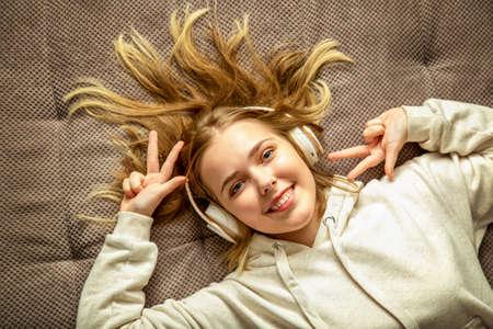 Happy millennial teen girl lying on comfortable sofa have fun moving enjoying listening music in earphones. Cute Young woman enjoying listening songs. Top view teenager girl smile flowing blond hair