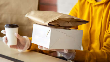 Woman in gloves work with takeaway orders. Waiters hands giving takeout meal while city covid 19 lockdown, coronavirus shutdown. Baking to go, takeaway Pizza coffee, Food delivery. Long web banner