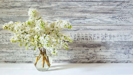White lilac bouquet in glass vase on wooden table. Spring branches of blooming lilac festive bouquet of flowers. Long web banner with copy space.