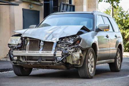 Crashed car in car accident. Broken vehicle after fatal disaster. Road collision damage. Gray car get damaged by accident. Damaged automobile after collision.