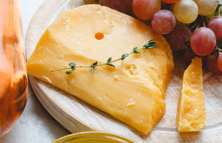 Cheddar cheese with grapes, pink wine, honey. Wine cheese snacks for a romantic dinner. Aged dutch gouda cheese on cheeseboard with cumin herbs on table. Banco de Imagens