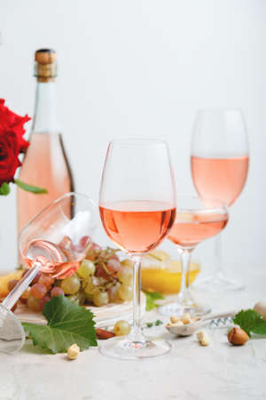 Rose wine in different glasses on light gray concrete background. Minimal Wine composition on white table. Banco de Imagens