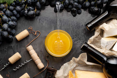 Honey in glass jar with honey spoon on dark stone board with wine cheese corkscrew in Black juicy grapes frame. Romantic dinner Wine Tasting with red wine cheese snacks on dark concrete background