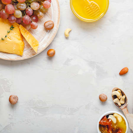 Wine composition on light gray rustic concrete background. Frame made of pink rose wine bottle cheese nuts and grapes honey. Camembert cheese, wine bar snacks for romantic dinner. Copy space