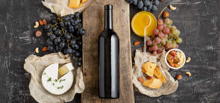 Red wine bottle on board, wine drink mockup. Frame made from Gastronomy different cheeses grapes honey nuts. Restaurant dinner, wine tasting gourmet snacks. Long web banner on dark concrete background