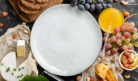 Round Plate blank or frame on grocery. Restaurant menu, template recipe. Mock up plate on full of food various table. Ceramic dish served in center appetizer ingredients meal. Long web banner