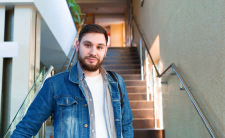 Student on brown stairs. Portrait of confident young man, caucasian handsome bearded man with backpack in reopen university campus hallway. Freelancer in modern coworking office Banco de Imagens