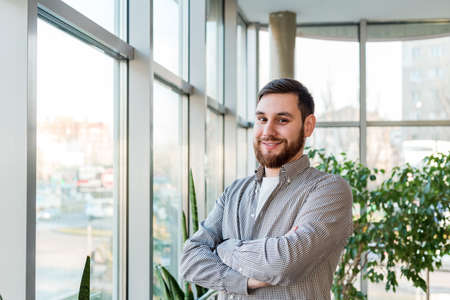 Smiling caucasian man standing near full length window in office alone. Successful bearded young smart man crossed arms. Handsome businessman in casual shirt. Freelancer in coworking space with plants Banco de Imagens