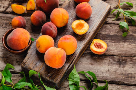 Peaches with leaves on a wooden board with peach in halves. Flat lay composition with ripe juicy peaches. Harvest of peaches for food or juice. Top view fresh organic fruit food with copy space Banco de Imagens