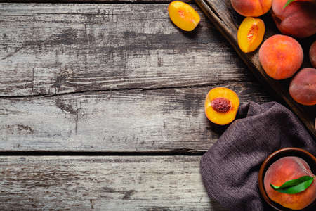 Peaches with leaves on dark wooden board with peach in halves. Composition with ripe juicy peaches. Food frame. Harvest of fresh organic fruit Flat lay on old rustic wooden table. Top view copy space