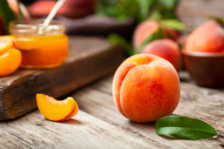 Peach fruit with leaf. Ripe juicy orange peach fruit on wooden table. Peach harvest and jam on rustic kitchen closeup in dark mood. Whole peach fruit and wedges for making jam