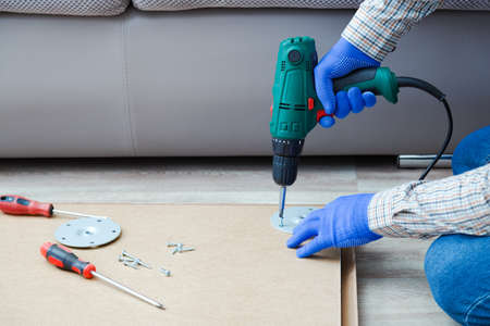 Electric Drill works in handyman hands at home. Male hands in gloves using electric drill tool to assemble and repair furniture. Home DIY. Copy space
