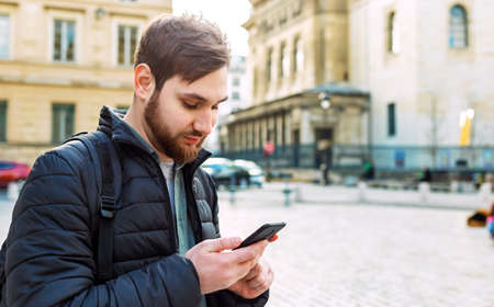 Attractive smart young man looking on smartphone. Man on street outdoors in Europe using mobile phone. Banco de Imagens