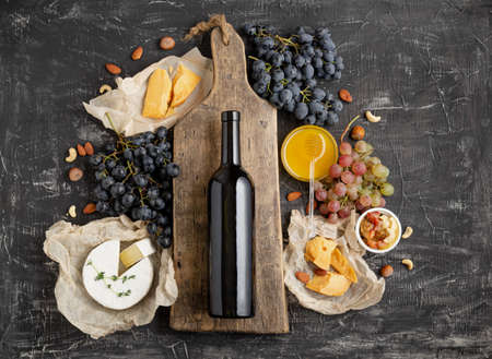 Red wine bottle on vintage cutting wooden board, wine drink mockup. Frame made from Gastronomy of different cheeses grapes honey nuts. Restaurant dinner, wine tasting on dark concrete background Banco de Imagens