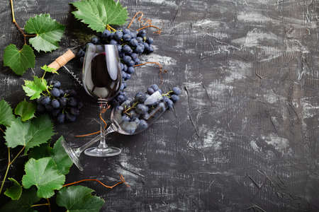 Wine glasses full of red wine and grapes. Wine bottles, grape bunches with leaves and vines corks on dark rustic concrete background. Flat lay wine composition on black stone table with copy space. Banco de Imagens