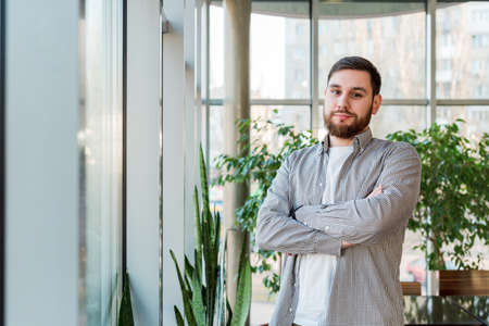 Caucasian man standing near full length window in modern office with plants, garden, greenhouse. Successful bearded young man crossed arms. Handsome businessman smart man in casual shirt