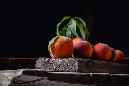 Still life peaches on wooden table cutting board knife Dark mood. Juicy ripe peaches on dark wooden rustic table. Delicious farm peaches with leaves whole fruit in halves, peach with bone Banco de Imagens