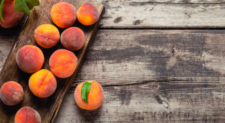 Still life peaches on wooden table cutting board. Dark mood. Juicy ripe peaches on dark wooden rustic table. Delicious farm peaches with leaves whole fruit Copy space Flat lay. Long web banner Banco de Imagens