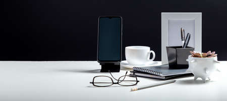 Home Office workspace. Desktop with smart phone template blank, notepads pens office suppliers cup of coffee drink plant. White work desk table on black background. Long web banner with copy space. Banco de Imagens