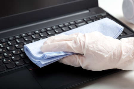 Female hands in gloves disinfecting laptop keyboard using wet disinfectant wipes. Woman cleaning keyboard from viruses bacteria prevent