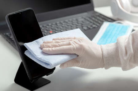 Woman in gloves wipes phomelaptop with wet tissue and disinfectant during . Disinfection phomeand laptop keyboard by alcohol disinfectant by woman in mask glowes on workplace, office desk.