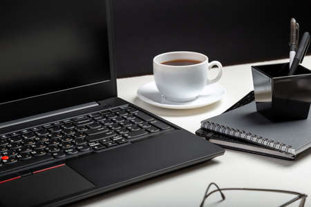 Black laptop on white table black background. Glasses, cup of coffee, office supplies. Home workspace for work or study in Office interior Banco de Imagens