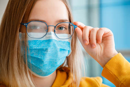 Foggy glasses wearing on young woman. close up portrait. Teenager girl in blue medical protective face mask and eyeglasses wipes blurred foggy misted glasses with copy space. New normal.