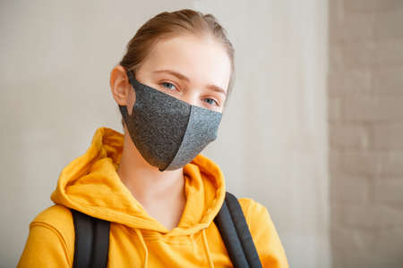 Happy student on brick wall background with copy space. Young beautiful woman smiles sincerely, wearing protective mask portrait with backpack. Teen Girl blonde Caucasian teenager traveler in mask Banco de Imagens