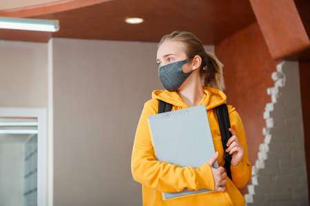 Young beautiful woman student wearing protective mask with backpack. Teen Girl blonde Caucasian teenager traveler in mask holding notebooks. Happy student in Reopen university campus lockdown
