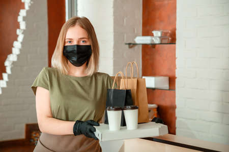 Woman waiter in protective medical mask and gloves work with takeaway orders. Waiter giving takeout meal while city lockdown, shutdown. Food Pizza coffee delivery Banco de Imagens