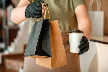 Waiter giving takeout meal while city lockdown, shutdown. Unrecognizable woman waiter, female hands in gloves work with takeaway orders. Food coffee delivery Banco de Imagens
