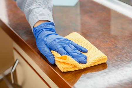 Woman wiping table countertop in kitchen by wet cloth rag. Female charwoman hand cleaning disinfect office home restaurant surfaces. Banco de Imagens